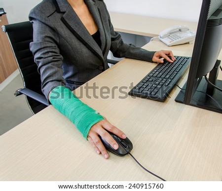 Injured businesswoman hand  clicking computer mouse and typing on computer keyboard.