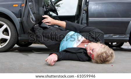 Injured driver with a laceration in her forehead, dropping unconsciously out of her car after having had an accident - stock photo