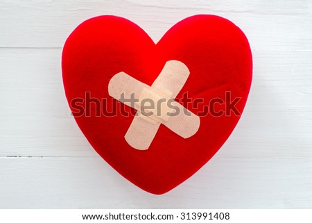 Injured heart with plaster on the white wooden surface - stock photo