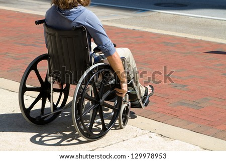 Injured male veteran sitting in his wheelchair rolls on the sidewalk.