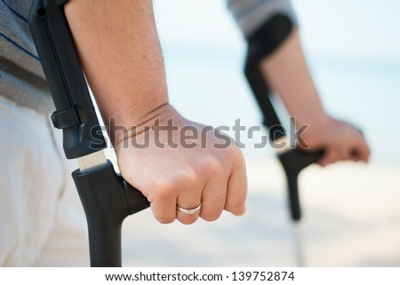 Injured Man Trying to walk on Crutches at a beach - stock photo