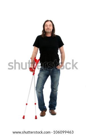 Injured middle-aged man standing holding a pair of crutches as he smiles his satisfaction with the way in which his rehabilitation is progressing