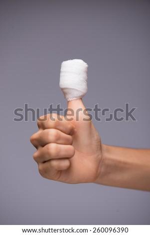 Injured thumb with white bandage - stock photo