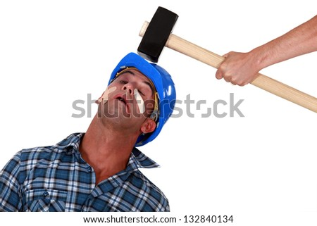 Injured tradesman being hit over the head with a mallet - stock photo