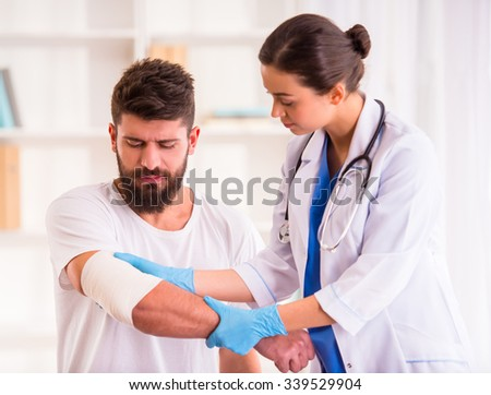 Injury hands. Young man with injured hands. Young woman doctor helps the patient - stock photo