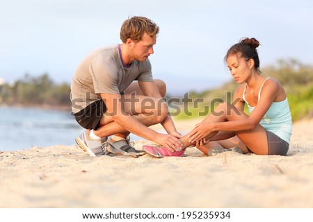 Injury - sports woman with twisted sprained ankle. Asian fitness female model sitting on beach sand getting help from Caucasian male touching her ankle. - stock photo