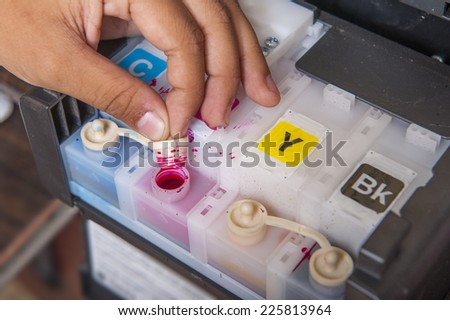 Ink jet printer cartridge refilling - stock photo