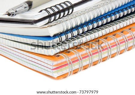ink pen at pile of notebook isolated on white background - stock photo