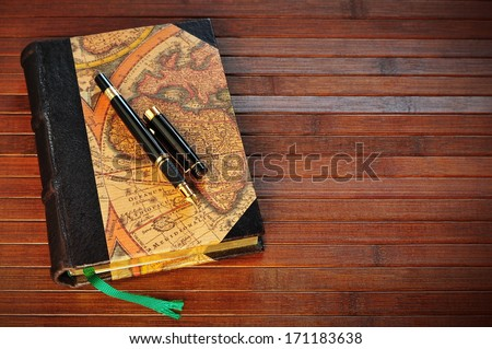 Ink pen on old aged book  - stock photo