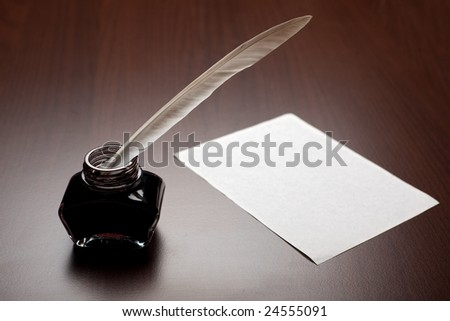 Ink, quill and an empty page on brown desk