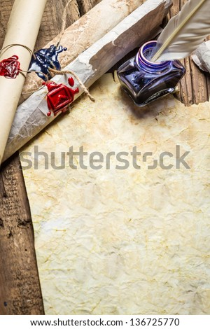 Inkwell and ancient scrolls on old sheet of paper - stock photo