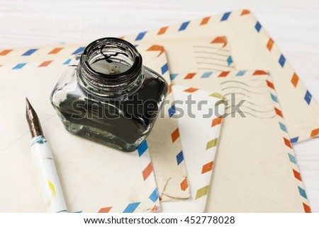 Inkwell, pen and vintage envelopes. - stock photo