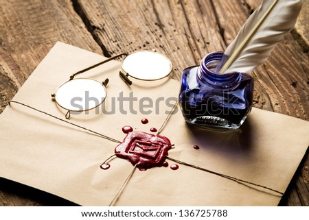 Inkwell with feather on envelope with red sealant and glasses - stock photo