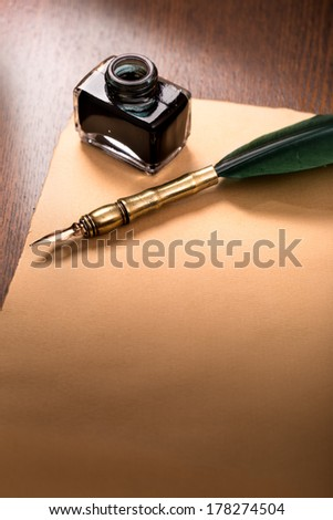 Inkwell with quill pen and paper on wooden table