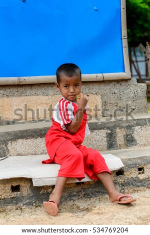 INLE LAKE, MYANMAR - AUG 30, 2016: Unidentified Burmese little boy n a red shirt. 68 per cent of Myanma people belong to Bamar ethnic group