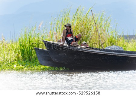 INLE LAKE, MYANMAR - AUG 30, 2016: Unidentified Burmese man in bamboo boat sails over the Inle Sap,a freshwater lake located in the Nyaungshwe Township of Taunggyi District of Shan State, Myanmar