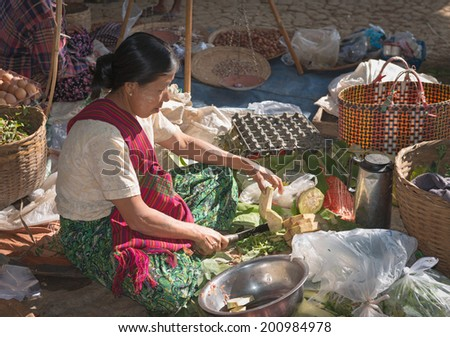 INLE LAKE, MYANMAR (BURMA) - 07 JAN 2014: Local Burmese Intha woman cut and sell vegetable on a traditional open market. Local markets serves most common shopping needs Inle Lake people. - stock photo
