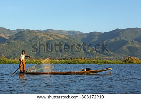 INLE LAKE, MYANMAR - DEC 7: Fisherman, Burmese man rowing a small boat at inle lake on Dec 7, 2014 in Inle. The known for their leg rowing techniques and the unique fishing equipment - stock photo
