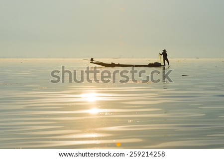 INLE LAKE, MYANMAR - FEB 26: A fisherman catches fish for food in sunrise on February 26, 2015 on Inle Lake, Myanmar. Intha people possess the feet-rowing style and the unique fishing equipment.