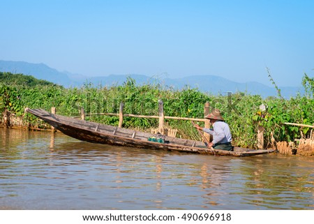 INLE LAKE, MYANMAR - 07 JAN 2014: Local man in a traditional canoe rows past floating gardens on Inle Lake, in Myanmar.