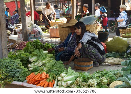 INLE LAKE, MYANMAR - MAR 1, 2015 - Young woman selling fresh vegetables at the weekly market on  Inle Lake,  Myanmar (Burma) - stock photo