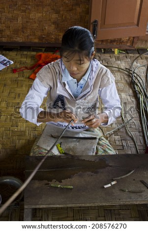 Inle Lake, Myanmar, March 6 2014:  hand-loom woman weaving on back-strap looms. .The Padaung people are one of the many minority tribes in Myanmar  known for  their craft procucts