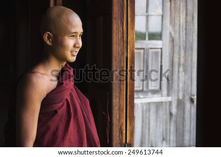 Inle Lake, Myanmar - March 23, 2014: Happy novice Buddhist monk looking out the window at Indein village monastery in Inle Lake, Shan State, Myanmar (Burma). - stock photo