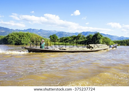 INLE LAKE, MYANMAR - November 23: Transporting bamboo over water. Agriculture in Myanmar is the main industry in the country, employing 65 percent of the labour force.