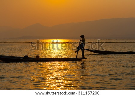 INLE LAKE VILLAGE MYANMAR : Silhouette People rows the wooden boat by his leg in Inle Lake