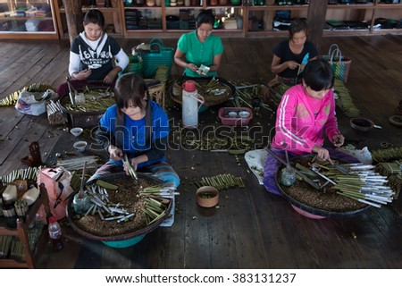 INLE, MYANMAR - 01 JAN 2014:  Women in work place rolling traditional hand made Burmese cigars
