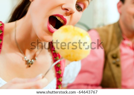 Inn or pub in Bavaria - young woman in Tracht eating dumplings she has put on her fork - stock photo