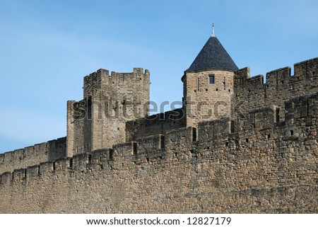 Inner and outer stone walls with towers of Carcasson castle, in sunlight against blue sky, France