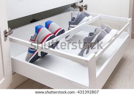 Inner drawer in a cupboard with divider and holder especially for shoes. Solution for shoe storage.