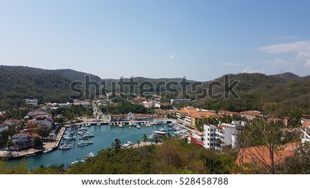 Inner harbor at at Bahia Santa Cruz in the Bahías de Huatulco tourist area in south western Mexico. Shown are the wharfs used by small commercial craft and the surrounding hotel infrastructure.