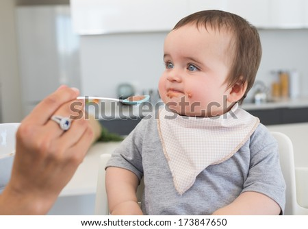 Innocent baby boy being fed by mother in kitchen - stock photo