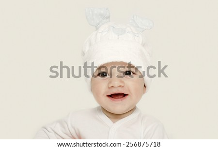 Innocent baby wearing a white hat looking adorable. Kid dressed for winter, lovely newborn. Adorable baby portrait looking curious.  Baby dressed as a funny bunny with a white hat with rabbit ears - stock photo