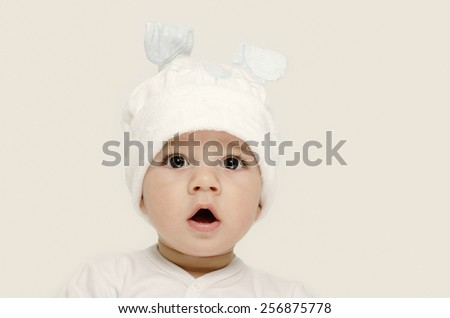 Innocent baby wearing a white hat looking adorable. Kid dressed for winter, lovely newborn. Adorable baby portrait looking curious.  Baby dressed as a funny bunny with a white hat with rabbit ears