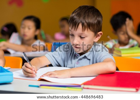 Innocent boy writing on book in classroom