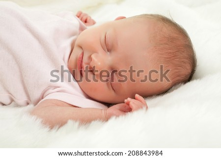Innocent little baby sleeping on a white furry blanket - stock photo