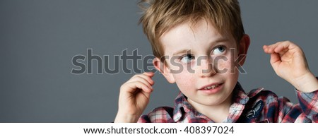 innocent thinking - closeup portrait of an adorable red hair little boy looking up, raising hands to ears for idea and imagination, copy space on grey background studio - stock photo