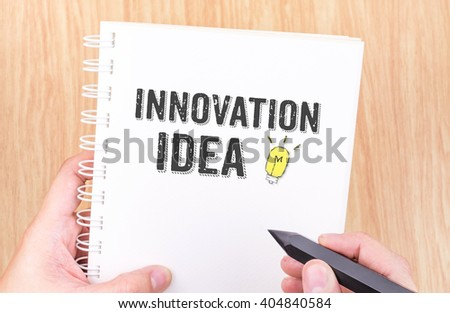 Innovation idea word on white ring binder notebook with hand holding pencil on wood table,Technology concept. - stock photo