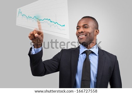 Innovative business. Cheerful young African man in formalwear pointing diagram on the transparent wipe board while standing against grey background - stock photo