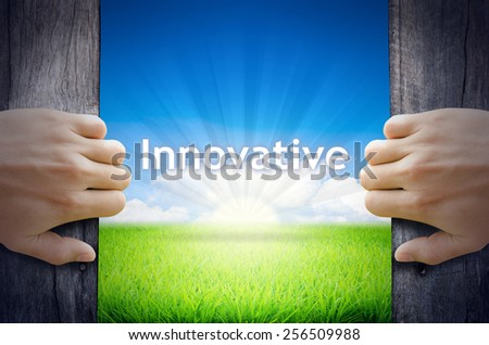 Innovative. Hand opening an old wooden door and found Innovative word floating over green field and bright blue Sky Sunrise. - stock photo