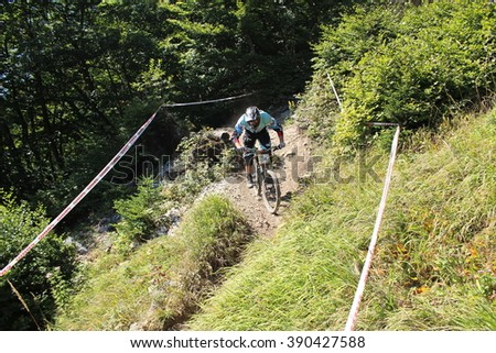 INNSBRUCK, AUSTRIA - AUGUST 29, 2015: Fully equipped professional biker is riding a mountain bike downhill style on Nordkette Alp mountain chain during the Nordkette Downhill Pro Competition. - stock photo