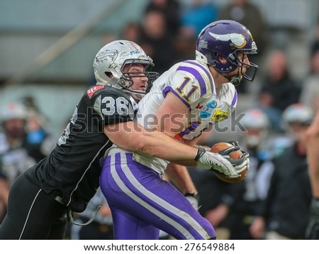 INNSBRUCK, AUSTRIA - MAY 3, 2014: TE Manuel Thaller (#11 Vikings) is tackled by DL Philipp Margreiter (#36 Raiders). - stock photo