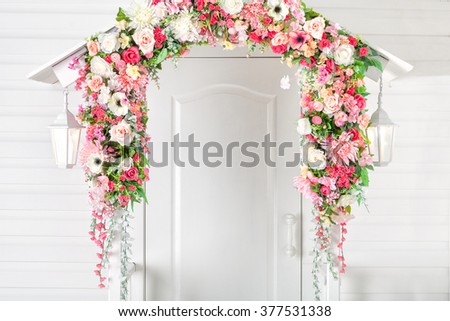 Input white door, porch and street lights . Flower arch. Spring. - stock photo