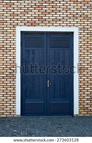 input wooden door in an old brick wall - stock photo