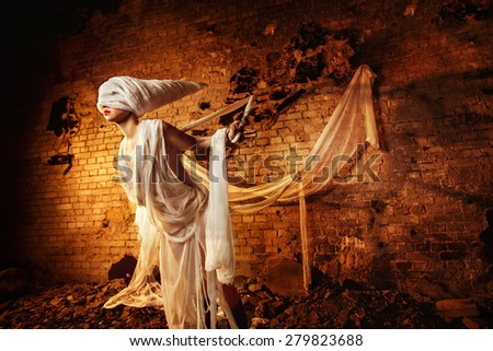 Insane evil creature in white bandage is tied to the dark bricks yellow wall background and stretching. - stock photo