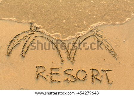 Inscription by hand RESORT in the beach sand in the surf line.
