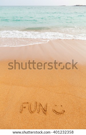 "Inscription ""FUN"" made on beautiful beach by the blue sea - stock photo"